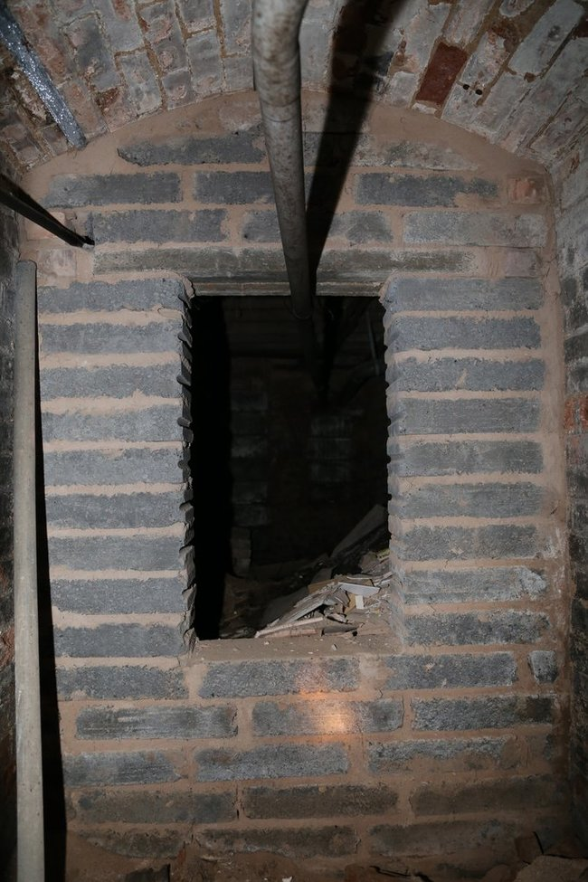 Room with a vaulted ceiling leading to more darkness.