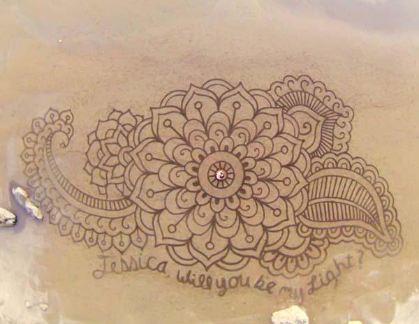 Ia menggunakan tali sebagai panduan untuk membuat pola geometris sambil menjelajahi mural pantai.