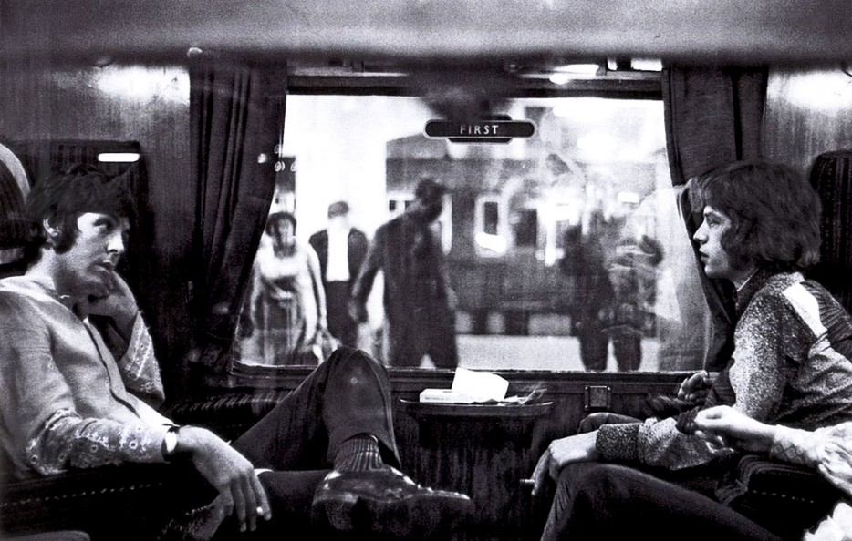 Paul McCartney and Mick Jagger sit opposite each other on a train to Bangor. (1967).