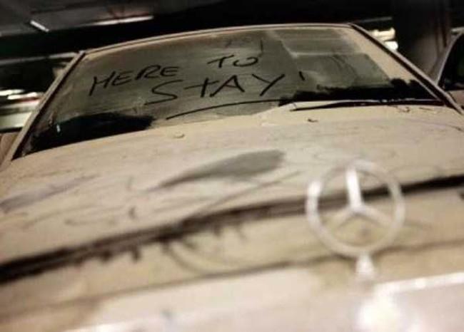 السيارات الرياضية المغبرة ، المهجورة منذ فترة طويلة ، تسد مواقف السيارات.