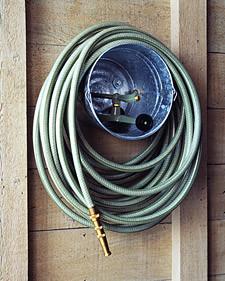 使用旧的水桶包扎软管并将其存储在墙上。